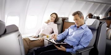 Ein Mann sitzt in der 747-8 Business Class und schaut in sein Notizbuch. Eine Frau entspannt // A man is sitting in the 747-8 Business Class and is looking in his notebook