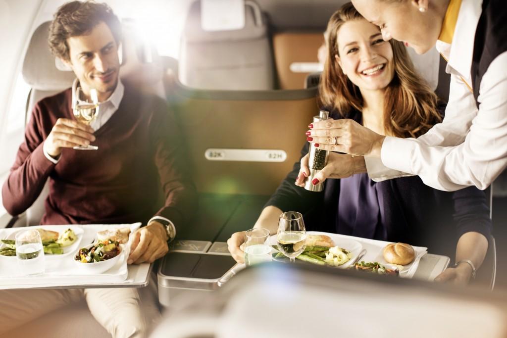 Flugbegleiterin würzt Essen des Fluggastes // flight attendant flavouring meal of passenger